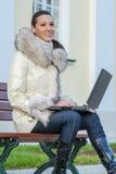 Frau im weißen Mantel, der auf Bank sitzt Lizenzfreies Stockbild