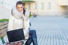 Frau im weißen Mantel, der auf Bank sitzt Stockfotografie