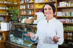 Frau im weißen Mantel, der Gesundheitsergänzungen im Drugstore fördert lizenzfreie stockfotografie