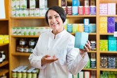 Frau im weißen Mantel, der Lebensmittelzusatzstoffwaren im Karton in d fördert lizenzfreie stockfotos
