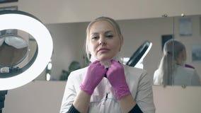 Frau im weißen Mantel und in den Handschuhen entfernt Maske im Salon stock footage