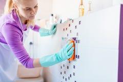 Frau im weißen Schutzblechreinigungs-Toilettendruckknopf lizenzfreies stockbild
