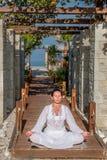 Frau im weißen Sitzen in der Lotoshaltung Lizenzfreies Stockfoto