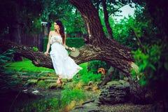 Frau im weißen Sitzen in einem Baum stockfotografie