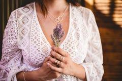 Frau im weißen Spitzehäkelarbeithemd, das einen Blumenstrauß des Lavendels mit silbernen Halsketten hält lizenzfreies stockbild