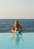 Frau im weißen Bikini meditierend auf Unbegrenztheitspool Stockfoto