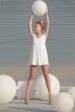 Frau im weißen Kleid mit weißem Ball Stockfotografie