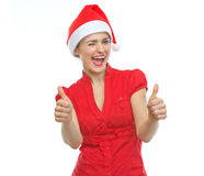 Frau im Weihnachtshut, der sich Daumen zeigt Lizenzfreie Stockfotos