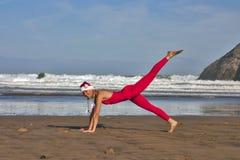 Frau im Weihnachtshut machen gymnastisch auf dem Strand Stockbild