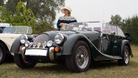 Frau im Weinlesekleid und im klassischen Morgan-Sportauto stockfotografie