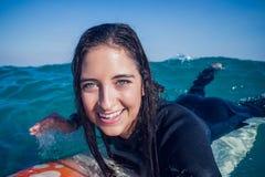 Frau im Wetsuit mit einem Surfbrett an einem sonnigen Tag Lizenzfreie Stockfotos