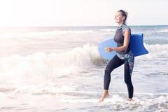 Frau im Wetsuit und Schwimmen verschalen das Gehen auf den Strand Stockfotografie