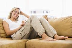 Frau im Wohnzimmer hörend zum MP3-Player Stockfotografie