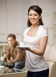 Frau im Wohnzimmer mit Ehemann Stockbild