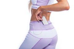 Frau im Yoga keucht mit Musikspieler in der Taschenrückseitenansicht Stockfotografie