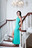 Frau inlong blaues Kleid, das im Stuhl sitzt Stockfotos