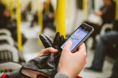 Frau insde Metrozug-Rohrlastwagen unter Verwendung des Smartphone, zum des m zu sehen Stockfotos