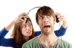 Frau interupts Mann mit Kopfhörern lizenzfreie stockbilder