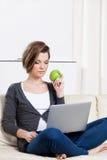 Frau isst einen grünen Apfel, der auf das Internet surft Lizenzfreie Stockfotografie