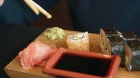Frau isst Sushi das Mädchen isst Rollen unter Verwendung der Stöcke stock video footage