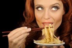 Frau isst Teigwaren Stockfoto