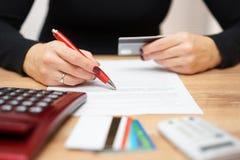 Frau ist Akkreditivbankkonto und Prüfung von Kreditkarte informat Lizenzfreies Stockbild