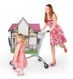 Frau ist beweglicher Einkaufskorb mit Haus Stockbild