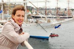 Frau ist an Bord der Lieferung am Hintergrund des Kanals Lizenzfreie Stockbilder