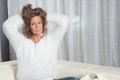 Frau ist, die mit den Händen in ihrem Haar hören Lizenzfreies Stockbild