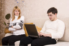 Frau ist mit Mann für Arbeitslaptop verärgert. Stockfoto