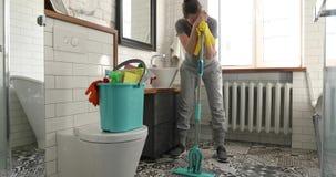Frau ist zu Reinigungsfliese in der Toilette müde stock footage
