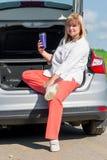 Frau 50 Jahre alt mit einem Getränk im Auto Stockfotografie