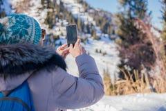 Frau 50 Jahre alte nehmende Foto in den Bergen im Winter, Alma Lizenzfreie Stockfotos