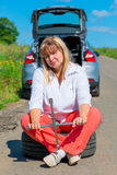 Frau 50 Jahre, die auf einem Ersatzrad nahe dem Auto sitzen Lizenzfreie Stockfotos