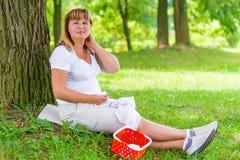 Frau 50 Jahre, die nahe dem Baum sitzen Lizenzfreie Stockfotografie