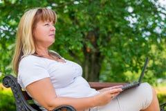 Frau 50 Jahre, entspannend im Park Stockbilder