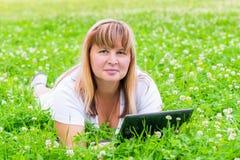 Frau 50 Jahre Lügen mit einer Tablette in einer Wiese Lizenzfreie Stockfotos