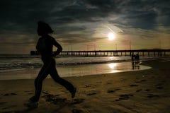 Frau joggs auf dem Strand Lizenzfreies Stockfoto