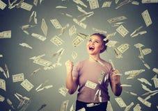 Frau jubelt die pumpenden Fäuste, die ekstatisch sind, feiert Erfolg unter dem Geldregen, der unten Dollarscheinbanknoten fällt stockfotos