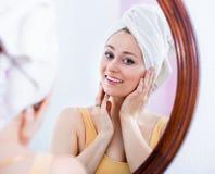 Frau kam von der Dusche und von der Stellung nahe bei dem Spiegel Stockfotografie