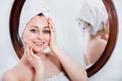 Frau kam von der Dusche und von der Stellung nahe bei dem Spiegel Lizenzfreie Stockfotos