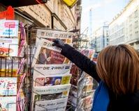 Frau kauft eine deutsche Zeitung Würfel Zeit von einem Kiosk Lizenzfreie Stockfotografie