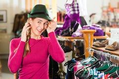 Frau kauft eine Kappe für ihren Tracht oder Dirndl in einem Shop Stockfoto