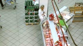 Frau kauft Würste in einem Supermarkt stock video