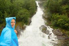 Frau kleidete in den Regenmantelstandplätzen nahe Wasserfall an lizenzfreie stockbilder