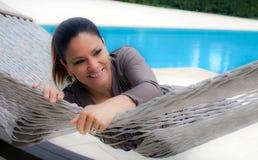 Frau kleidete in der Silber-grauen Entspannung auf einer Hängematte an Stockfoto