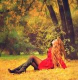 Frau kleidete im roten Mantel an, der im Herbstpark sich entspannt Stockfoto