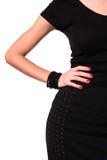 Frau kleidete mit dem schwarzen Kleid an, das an mit der Hand überzeugt steht Stockfotografie