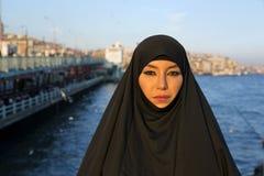 Frau kleidete mit schwarzem Kopftuch, Chador auf Istanbul-Straße, Truthahn an Stockfotos