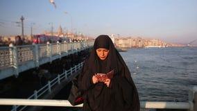 Frau kleidete mit schwarzem Kopftuch, Chador unter Verwendung des Handys, Istanbul an stock video footage